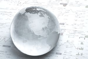 a glass globe on financial charts