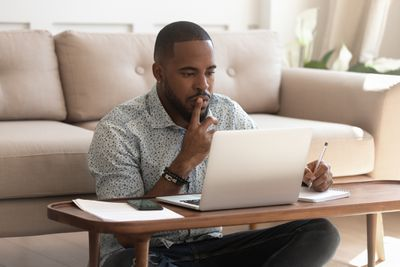 Concentrated young african american black guy sitting on heated floor at modern coffee table in living room, looking at laptop screen, online courses studying, listening to coach, writing down notes.