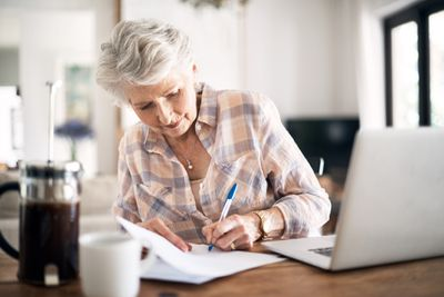 Woman making notes on paper while working on laptop