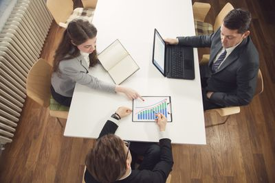 Co-workers analyzing financial statistics together at a table in an office