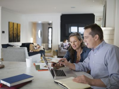 Couple using laptop at kitchen table while they work on the family budget