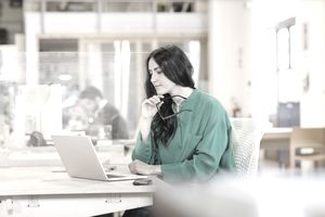 Businesswoman looking at laptop while sitting at desk