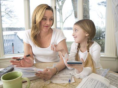 A woman works on her taxes with her young daughter who is holding a calculator