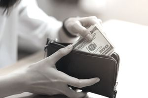Woman Putting Paper Currencies In Purse