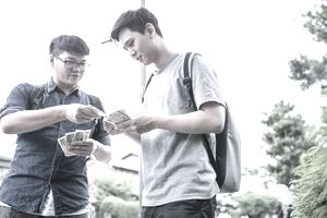 Young man handing dollars to and lending money to friend