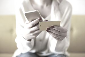 close up of a person's hands holding a credit card and a smartphone