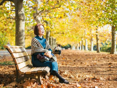 Older woman on a fixed annuity enjoying the fall weather on a park bench.