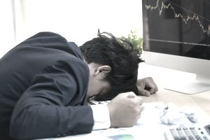 An upset forex trader clinches his fist and pounds his head on desk near a computer monitor, crumpled papers and a calculator