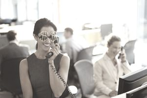 a woman wearing dollar sign glasses talking on the phone