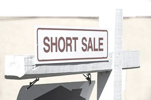 "Closeup of a ""Short Sale"" sign on a post in front of a house"