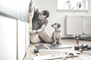Man doing home improvements while dog watches