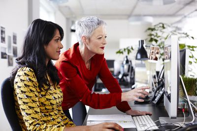 Female mentor helping another woman at work