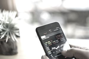 Hand holding a mobile phone to check stock data