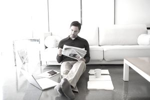 Man on floor of living room reading business section of newspaper about retail stocks