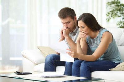 Worried couple reading a letter