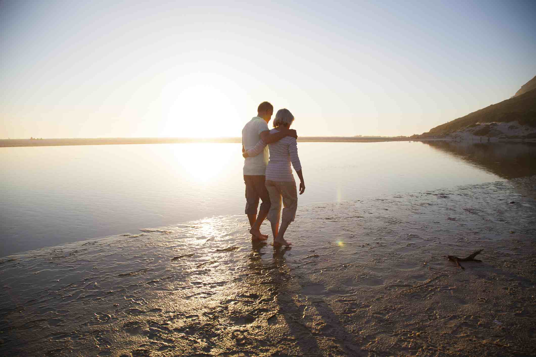 A couple walks on a quiet beach at sunset