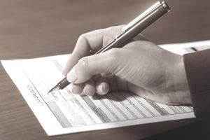 A person completing a loan application with a fountain pen