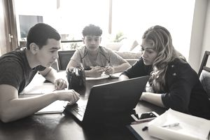 Woman showing teenage boys information on computer at home