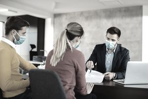 agent with face mask explaining terms of a contract to a couple during the meeting