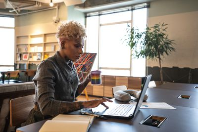 A student with blond hair and tattoos holds a coffee cup while using a laptop in a library