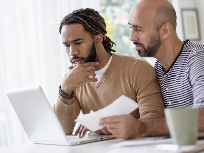 Two men are sitting at a table and are working on a laptop. One is holding a check.