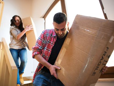 Serious couple moving fragile boxes during a move