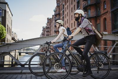 Couple wearing helmets and backpacks riding e-bikes over a bridge, with brick buildings in the background