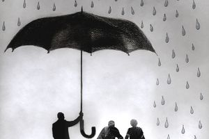 Businessman holding umbrella protecting elderly couple