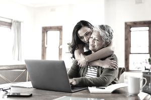 An older woman is working on a laptop. A younger woman is hugging her affectionately.