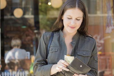 Woman placing money into her wallet