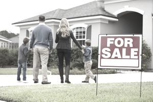 "Young family standing in driveway of house with a ""For Sale"" sign"