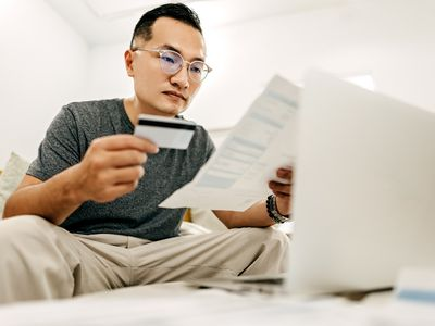Person with glasses looking at credit card bill while holding a card.