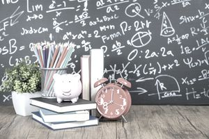 Piggy bank on a stack of books with other school supplies and a chalkboard