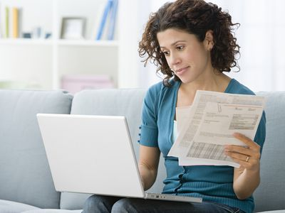 Woman reviewing paper statements and online records