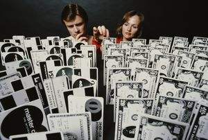 A man and a woman choose from an array of credit cards and dollar banknotes, 1979.