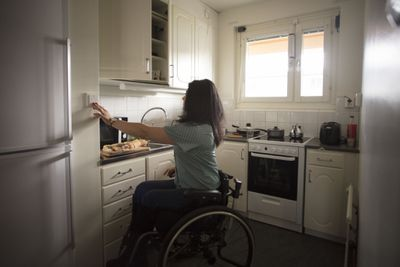 Woman in a Wheelchair Pushing a Button on the Wall in Her Kitchen