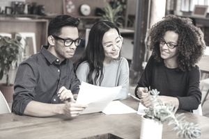 A man and two women review a document while sitting at a table