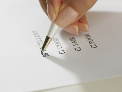Hand filling out a ratings checklist