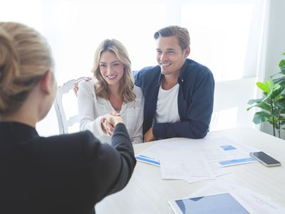 Real estate agent with couple closing a deal