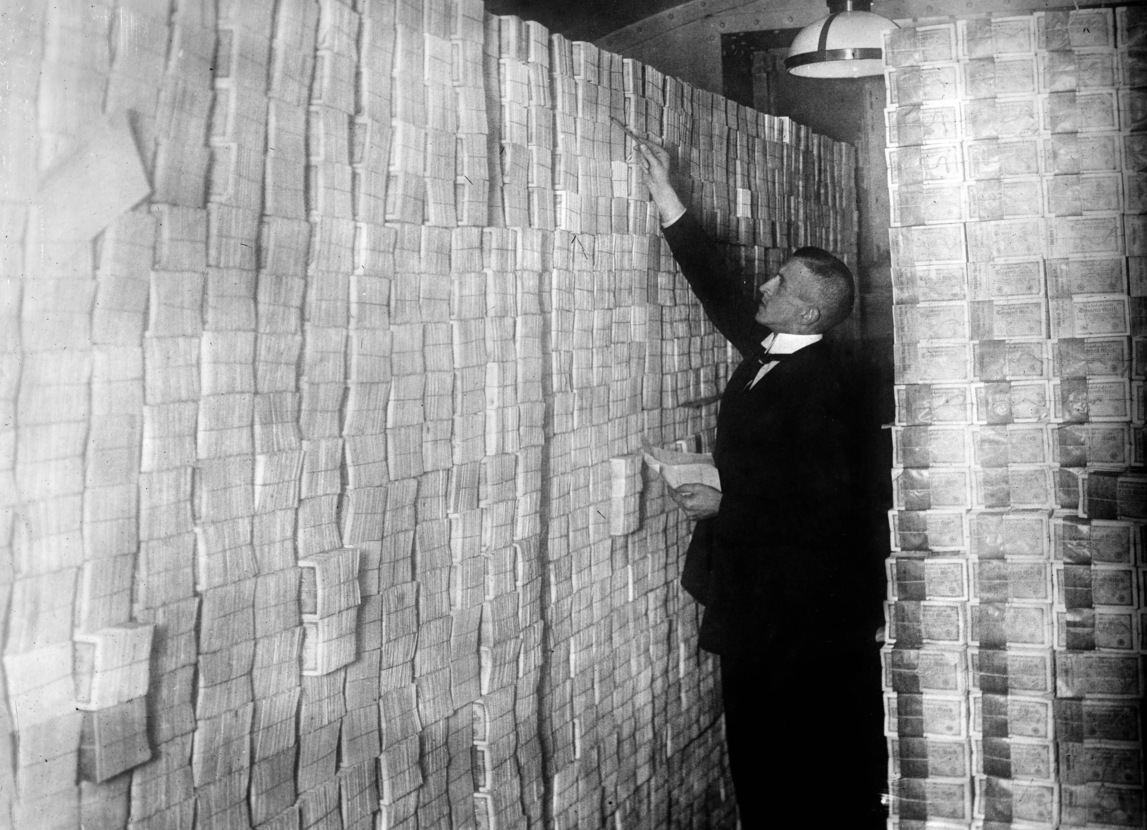 Image of piles of bank notes taller than the man counting them in a bank in Berlin