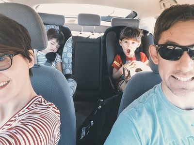 Mom taking selfie of the family in a car on a road trip with two kids in the back seat and the father driving.