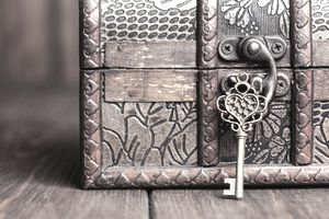 Closeup of a vintage key and old treasure chest on wooden table