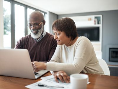 Couple using a laptop in their living room to look at their financial budgets
