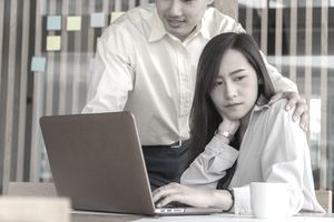 Uncomfortable Businesswoman Looks Away from Colleague Who Has His Hand on Her Shoulder