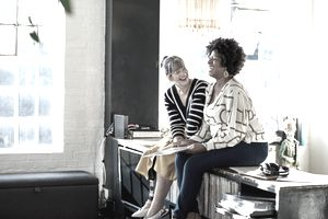 Two mature women laughing sitting on countertop of bright loft apartment