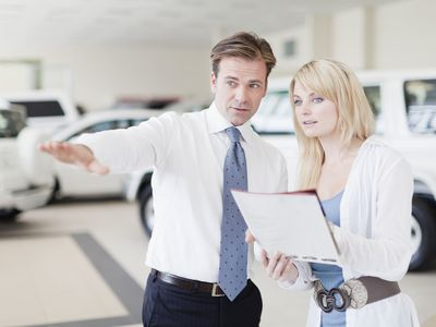 Car salesman shows cars and reviews payment plans with a customer.