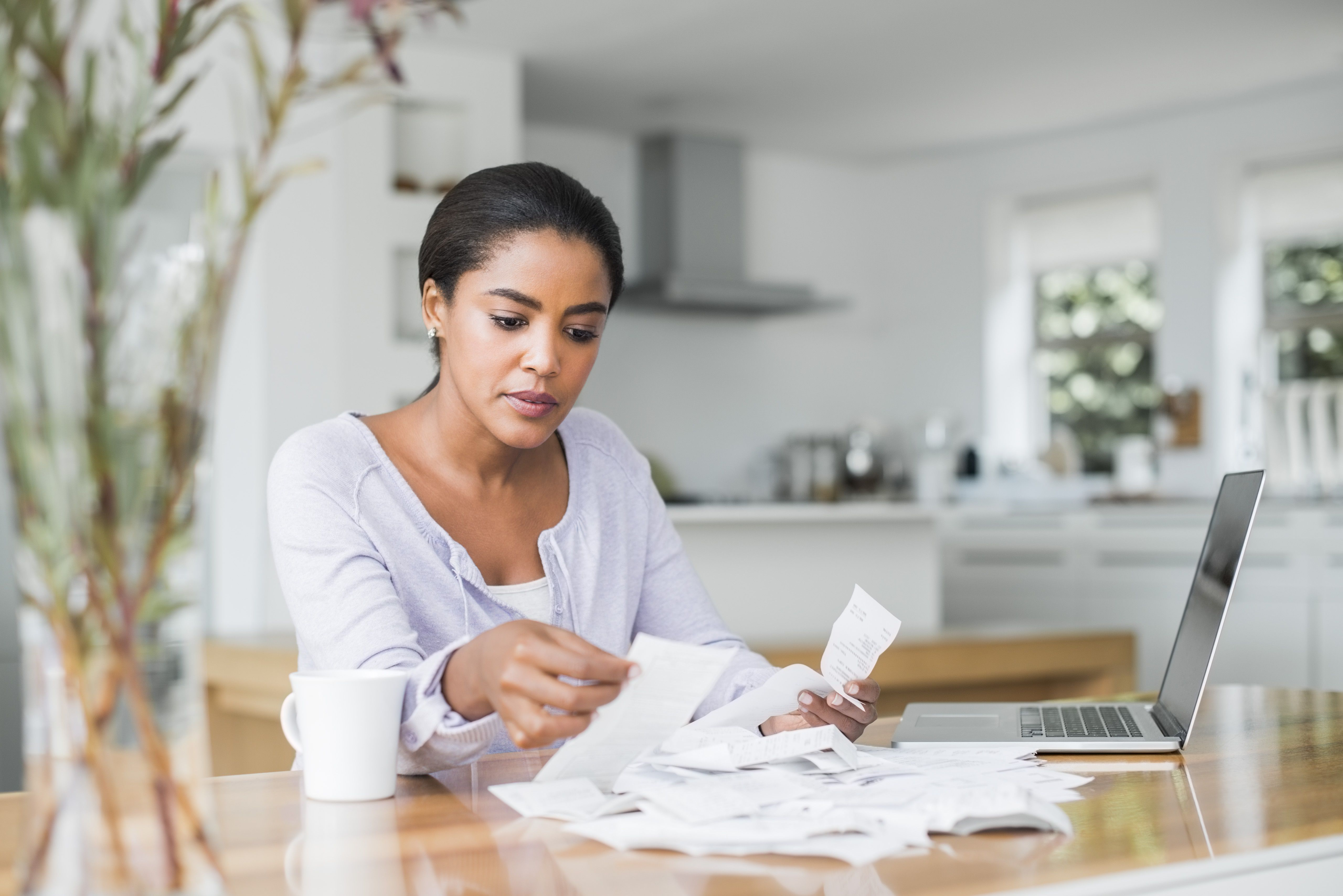 A woman pays bills online at home