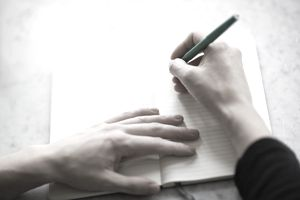 close-up of hands writing in notebook