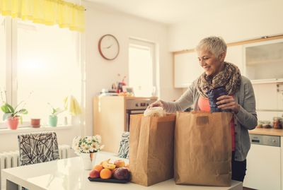 Woman stands smiling at paper shopping bags filled with groceries on kitchen table