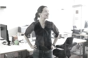 A woman beams with pride in a well lit office space.